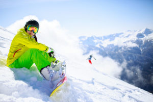 Snowboarder sitting with mountain chain in the background.